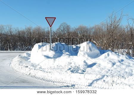 The winter. The snowcapped trees. The cool temperature. The sky is blue. Traffic sign. Snow. Road.