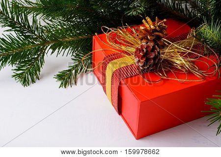 Christmas background with golden decorated red gift box. Christmas greeting with fir branches and gift box with golden cord and pine cones.