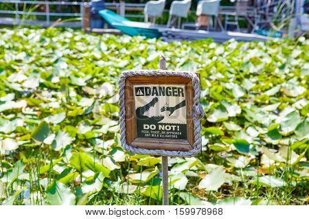 Caution warning sign. Do not feed alligators. On alligator farm in Florida Everglades National park, USA warning visitors not to feed animals