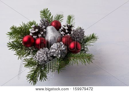 Christmas decoration with red glitter ornaments and silver mash. Christmas table centerpiece with pine cones and silver pear.