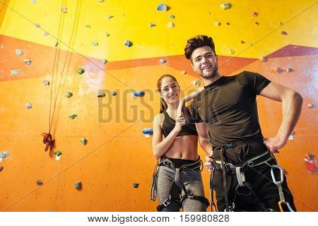 Happy together. Overjoyed active young man and woman posing while standing in climbing gym and preparing to training.