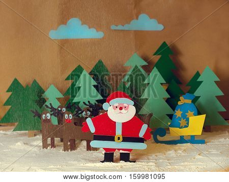 Funny Santa cut from colored cardboard with reindeer and sleigh with gifts in the forest