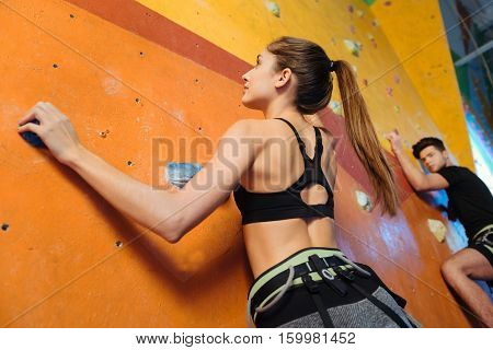 Happy times together. Joyful athletic young man and woman climbing up the wall while training and spending time in climbing gym.