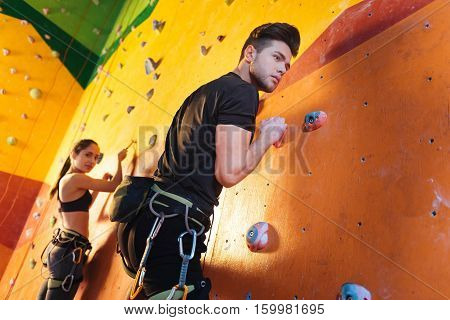 Cooperation and fun. Concentrated athletic young man and woman climbing up the wall while training and spending time in climbing gym.