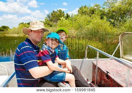 Two little kids boys and father making air boat tour in Florida wetland swamp at Everglades National Park in USA. Family, dad and children discovering wild nature and animals. Family having fun.