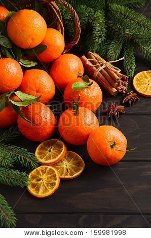 Fresh tangerine clementine with spices on dark wooden background, Christmas concept, selective focus, vertical
