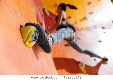 Strong legs. Young flexible pretty woman training hard in climbing gym while using equipment and climbing up the wall.