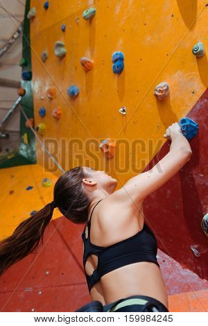Be active. Beautiful young active woman training hard in climbing gym while using equipment and climbing up the wall.