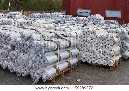 Shipment, logistics, delivery and product distribution business industrial concept: storage warehouse with rows of stacked rolls on wooden shipping pallets.