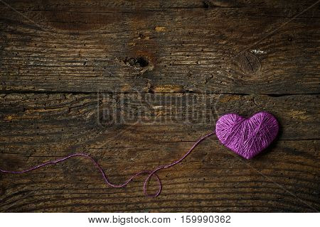 Purple Heart with a ball of thread on on old shabby wooden background. Image of Valentines day