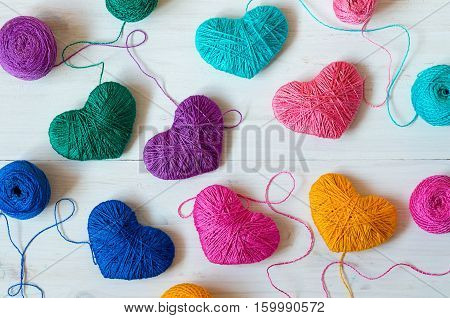 Multicolored Hearts with a balls of thread on wooden background. Image of Valentines day