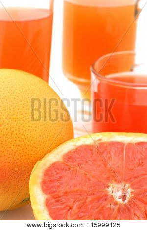 cutted grapefruit with three glass of grapefruit juice on background