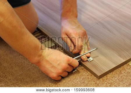 Assembling furniture. The image of a man who by means of a screwdriver engaged in the Assembly of furniture.