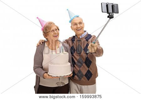 Joyful seniors with party hats and a birthday cake taking a selfie with a stick isolated on white background
