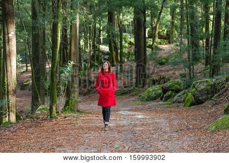 Young woman walking alone on a forest dirt path wearing a red overcoat on a cold winter day