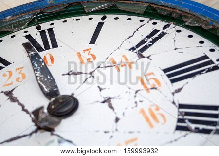 Close up detail of an old damaged retro clock, with broken face, hands and glass, and with roman numerals