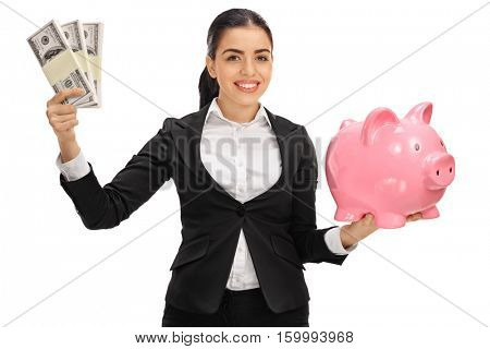 Delighted businesswoman holding money bundles and a piggybank isolated on white background