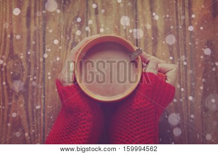 Woman holding cup of hot cacao or coffee on wooden background Closeup of hands in warm red sweaters. Top view. Toning image.