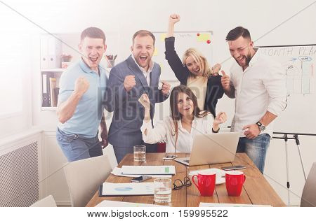We win. Happy business people celebrate success near laptop screen in the office. Successful corporate team of partners and coworkers, winners