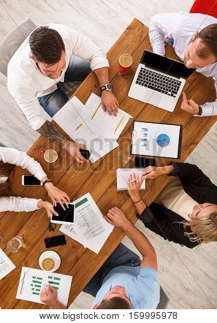 Group of busy business people meeting in office, top view of wooden table with mobile phones, laptop, tablet and documents papers with diagram. Men and women team together have brainstorm discussion.