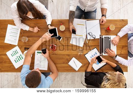 Group of busy business people working in office, top view of wooden table with mobile phones, laptop, tablet and documents papers with diagram. Men and women team together have brainstorm discussion.