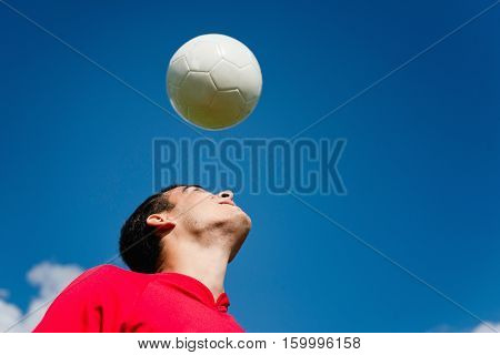 Soccer player with ball, toned image, blue background