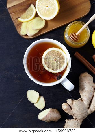 Antiviral healthy ginger tea with lemon and honey on dark background. Top view. Useful Healthy drink