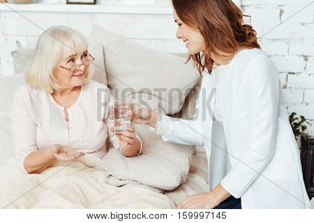 Kind hearted. Positive professional nurse holding glass of water and visiting sick elderly woman at home while she is lying in bed