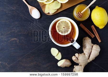 Antiviral useful drink ginger tea. Healthy drink. With lemon, honey and slices of ginger on wooden table . Top view. Rustic Style. View from above.