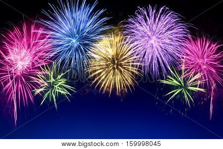 Gorgeous multi-colored fireworks as an arch shaped border on dark blue background ideal for New Year or other celebration events