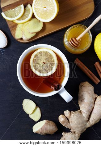 Antiviral ginger tea with lemon and honey on dark background. Top view. Healthy drink. Creative composition.