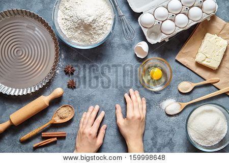 Work with the dough. The kitchen table with raw ingredients, rolling and baked pin. The woman's hand ready to knead the dough