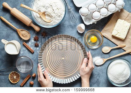 The process of making pie dough by hand. Baking ingredients for homemade pastry on dark background. Bake sweet cake dessert concept. Top view, flat lay