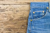 Blue jeans on brown wooden background.Close up of blue jeans Blue Jeans texture.Blue denim jeans texture. Jeans background. Blank leather jeans label sewed on a blue jeans. poster