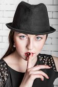 Close-up portrait of young woman in hat placing finger on lips gestures silently quiet shhhhh secret facial expression human emotions signs and symbols poster