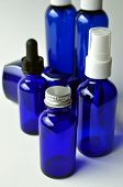 Group of dark blue glass bottles for cosmetic lotions, serums, oils and liquids poster
