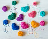 Multicolored Hearts with a balls of thread on wooden background. Image of Valentines day poster