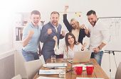 We win. Happy business people celebrate success near laptop screen in the office. Successful corporate team of partners and coworkers, winners poster