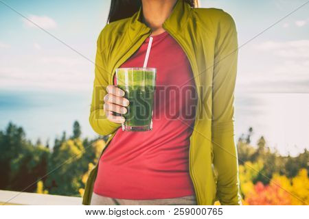 Green smoothie breakfast detox diet food cleanse juice drink. Woman eating healthy for weight loss, morning meal outside in autumn nature.