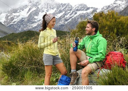 Camping lifestyle young people eating lunch outdoors hiking on New Zealand mountain trail track. Couple trampers tramping in nature with backpacks.