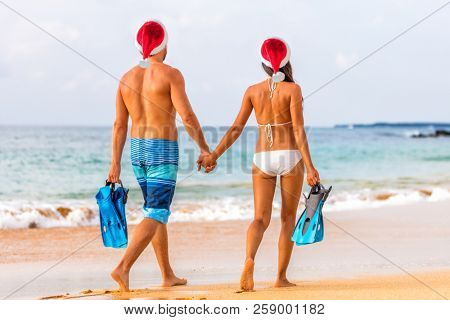 Christmas beach couple caribbean winter holiday couple wearing santa hats on exotic vacation. Young people going swimming with snorkel. Snorkeling water sport fun.