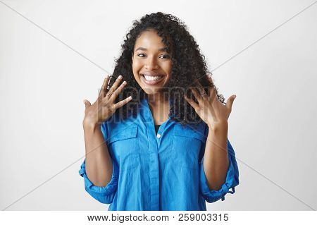 Portrait Of Attractive Young Dark Skinned Female In Blue Shirt Having Excited Facial Expression, Smi