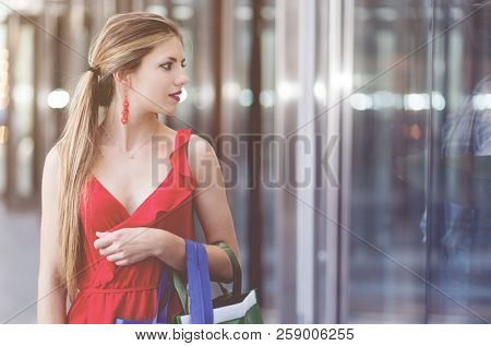 Beautiful young woman in a red dress holding shopping bags and checking a store outdoor in a modern city setting