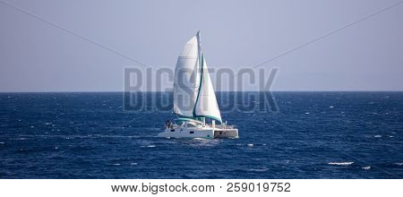 Sailboat travels with wind help, in calm sea. People enjoy the sailing, blue sky background, banner.