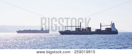 Two container ships for international transport sail full of cargo. Sea commerce, blue sky background, banner.