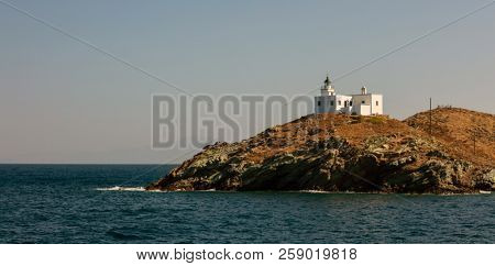 Lighthouse and agios Nikolaos church on rocky land. Kea,Tzia the sunny island, Greece. Blue sky background, banner.