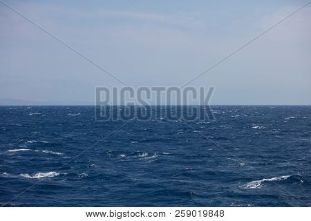 Windy day, stormy dark blue sea and waves. Blur mountains and cloudy sky background.