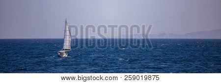 Race of two sailboats with wind help, in calm sea. Clear blue sky and mountains background, banner.