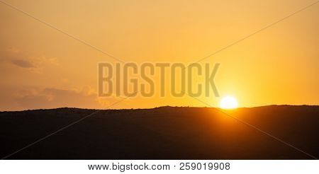 Sunset, sunrise over mountains silhouette. Scattered clouds on colorful sky background, space, banner.