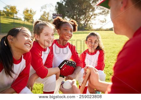 Girl baseball team in a team huddle with coach, listening